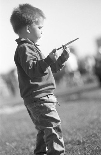 Discovery learning - A child explores the flight behavior of a toy aircraft from Styrofoam