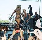 Blonda virino staras en sceno dum viro, kiu ankaŭ havas blondan hararon, subskribas malantaŭ ŝi.