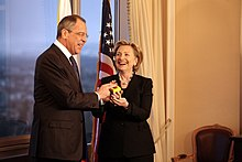 "Hillary Clinton standing with Russian Foreign Minister Serguéi Lavrov. Both of them are holding a ""reset button"". They are in a room with a window to the left and an American flag behind them"