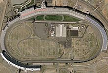An aerial view of an oval-shaped motor-racing circuit.