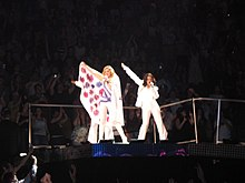 A blond woman in a white and purple leotard and a cape, which she opens up towards audience in front of her. She is flanked by two similarly dressed women.