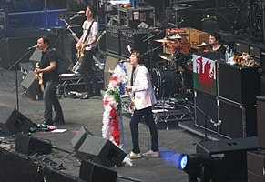 Manic Street Preachers in 2010. From left to right: James Dean Bradfield, touring member Wayne Murray, Nicky Wire and Sean Moore; the open microphone on the far right is a traditional memorial to former member Richey Edwards, who disappeared in 1995.