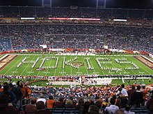 "Marching band members stand an spell the word ""Hokie"" filling the whole of the stadium's playing field in front of thousands of fans in their seats."