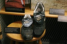 "Dark baseball cleats with the NIKE brand name bearing the silver signature ""Mariano Rivera MVP"" sit on a wooden stool"