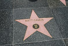 Pink granite star on a black granite side-walk.