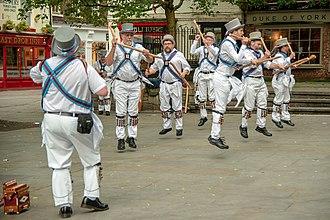 Tourism in Yorkshire - Morris dancers entertain tourists on a York street corner near The Shambles