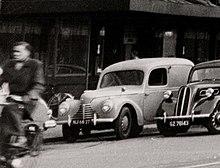 Černobílá fotografie dodávky Škoda 1101 zaparkované na ulici neznámého nizozemského města, vpravo od ní Ford Anglia E04A z let 1939–1948. V popředí vlevo jede muž na bicyklu.