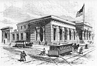An Egyptian-Revival-style building on a street corner, with doric columns on its façade and a large flag flying atop a mast. Pedestrians are seen navigating two horse-drawn trams, which travel on lines that bisect intersecting streets.