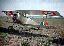 A white biplane fighter aircraft, with (in order of increasing size) blue, white and red concentric circles as the insignia on its wings, siting in a field of dirt