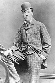 Oscar Wilde posing for a photograph, looking at the camera. He is wearing a checked suit and a bowler hat. His right foot is resting on a knee high bench, and his right hand, holding gloves, is on it. The left hand is in the pocket.