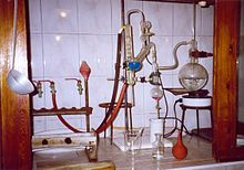 A glass apparatus is located in a gas hood covered with tiles.  From right to left: A round bottom flask, electrically heated from below, in which a clear liquid is boiling.  The vapor of the liquid is directed into a smaller flask with a red liquid.  From there, a glass tube leads, first rising vertically and then sloping downwards, into another flask, where it is immersed in a blue liquid that has been stirred up by the rising bubbles.  The tube is encased in a second tube that guides the resulting gas into a vertical spherical cooler.  The cooler is connected to the water connections in the gas exhaust.  Condensed liquid drips from the cooler into an open beaker.  A plastic pipette is placed in the beaker.  In the foreground is an unlabeled glass bottle with a clear liquid and a rubber ball as a pipette aid.