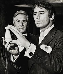 A black-and-white photograph of two well-dressed men examining a small wooden object.