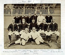 Two rows of men, one standing behind one seated, of men wearing old-style white baseball uniforms and striped pillbox caps
