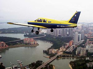 A Piper Warrior II in the SYFC livery flying over central Singapore