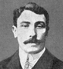 31-year-old man with a moustache. He is wearing a suit and tie