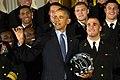 President Barack Obama holds a U.S. Naval Academy football helmet while inspecting a team ring. (26444075770).jpg