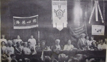 A black and white photograph depicting the head table at a women's conference surrounded by seated delegates above whom are suspended flags of various nations
