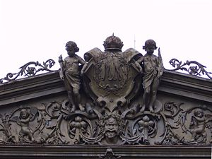Mangkunegaran Palace - Mangkunegaran coat of arms flanked by European-style cherubins and dvarapala face below