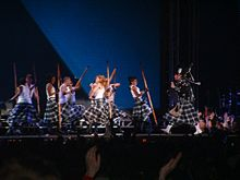 Faraway image of several individuals wearing white shirts and kilts holding poles. The backdrops show a blueish image.
