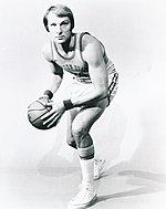 A man wearing a basketball uniform stands with his legs facing his right and holds a basketball aligned with his legs.