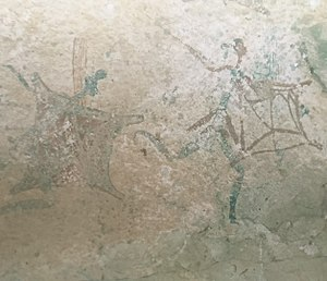 Bantu expansion - San rock art depicting a shield-carrying Bantu warrior.  The movement of Bantu settlers, who migrated southwards and settled in the summer rainfall regions of Southern Africa within the last 2000 years, established a range of relationships with the indigenous San people from bitter conflict to ritual interaction and intermarriage.