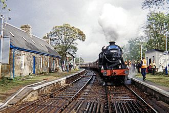 Forsinard - Forsinard railway station in 1998 with the RSPB visitor centre at left and a southbound steam hauled excursion taking water.