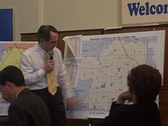 Senator Joe Dunn pointing out clusters on a map of businesses that have permits to emit pollution