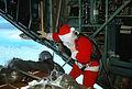 Santa Clause (Capt. Mike d'Albertis, 605th Military Airlift Support Squadron) and Staff Sgt. Tony Thompson, loadmaster with the 21st Tactical Airlift Squadron, watch as a Christmas Drop container is parachuted DF-ST-82-01802.jpg