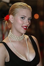 A picture of Scarlett Johansson wearing a black dress and a pearl necklace.