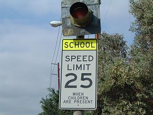 A speed limit sign entering a school zone, alo...