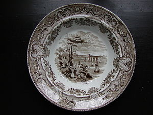 Stoneware - A Staffordshire stoneware plate from the 1850s with white glaze and transfer printed design.
