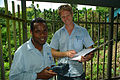 Solomon Water volunteer and his counterpart Josh Torenn use the AusAID funded PH tester at the Kongulai water source. (10721858923).jpg