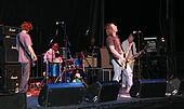 Five men on a stage; three in the forefront are holding guitars, while two in the background are behind a drum set and other equipment. Speakers, microphone stands and other equipment are also visible.