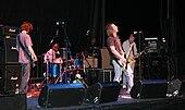 Cinq hommes sur une scène;  trois à l'avant-garde tiennent des guitares, tandis que deux à l'arrière-plan sont derrière une batterie et d'autres équipements.  Les haut-parleurs, pieds de microphone et autres équipements sont également visibles.