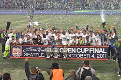 Several players are standing together with three trophies on the ground in front of them.
