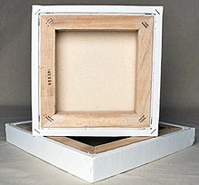 A square canvas rests atop another with its back showing a thick frame of wood.