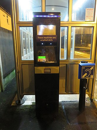 Permit to travel - A Metric Aura PERTIS machine at Spondon station, with one LCD panel displaying messages, time and money entered. This machine  has two coin reject buttons. Note that this machine has been vandalized as the cover over the interaction area is missing. Photographed on 8 February 2016.