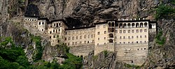 Photograph of a large, multi-story monastery built into a cliff face.