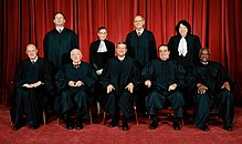 Nine judges in black robes pose for a photograph, five are seated, four stand behind them.
