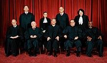 Negen Rechters in zwarte gewaden poseren for an foto, Vijf Zitten, vier tribune achter hen.