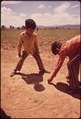 THE CHILDREN OF MIGRANT WORKERS PLAY MARBLES WHILE THEIR PARENTS WORK IN FIELDS - NARA - 543855.tif