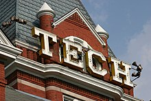 "Large, white, capital letters spelling ""TECH"" situated just below the pointed roof of the square, red brick tower of the administration building"