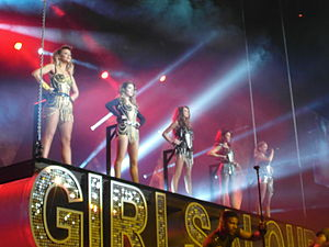 "Five young women in bright leotards standing atop a sign reading ""Girls Aloud"""