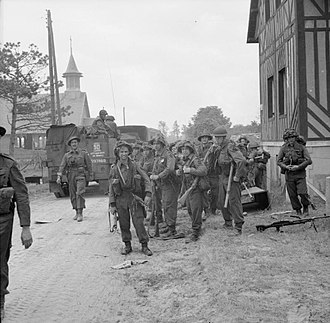 3rd Division (United Kingdom) - Men of 2nd Battalion, Royal Ulster Rifles pause during the move inland from Sword Beach, 6 June 1944.