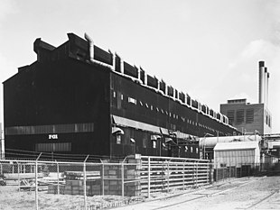 A large dark-coloured rectangular building and a smaller building with three smokestacks