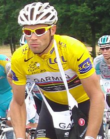 A road racing cyclist wearing a yellow jersey with a white section on the chest, which contains rainbow stripes as well. He has a musette bag on over his head, and other cyclists are visible in the background.