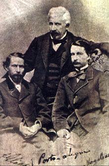 Uma fotografia velha que descreve dois homens de cabelos escuros sentado em primeiro plano e um homem de cabelos brancos em pé atrás