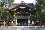 Frontal view of a black wooden gate with a large dominating roof with an undulating gable and golden metal decorations.