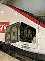 Trappe d'accès au système commandant l'ouverture ou la fermeture des trappes protégeant l'attelage automatique, sur une rame TGV POS du service Lyria à l'arrêt en gare de Lyon-Saint Exupéry (juin 2019).jpg