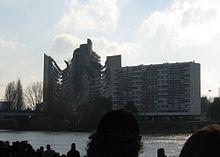 Une foule observe, sur la rive opposée de la Loire, un bâtiment d'une quinzaine d'étages s'effondrant.